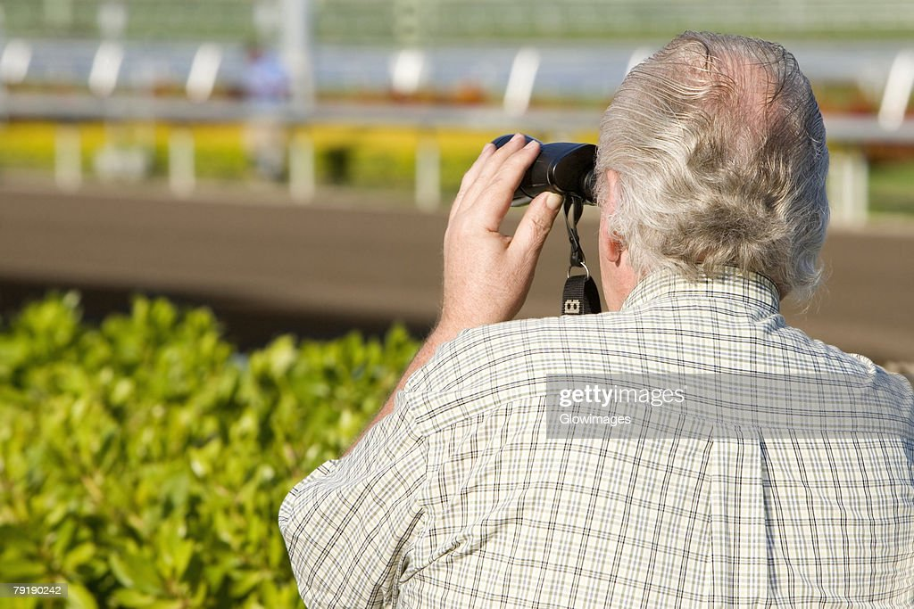 Rear view of a spectator looking through a pair of binoculars at the horseracing track : Stock Photo