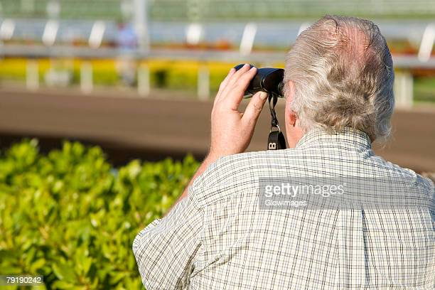 Rear view of a spectator looking through a pair of binoculars at the horseracing track