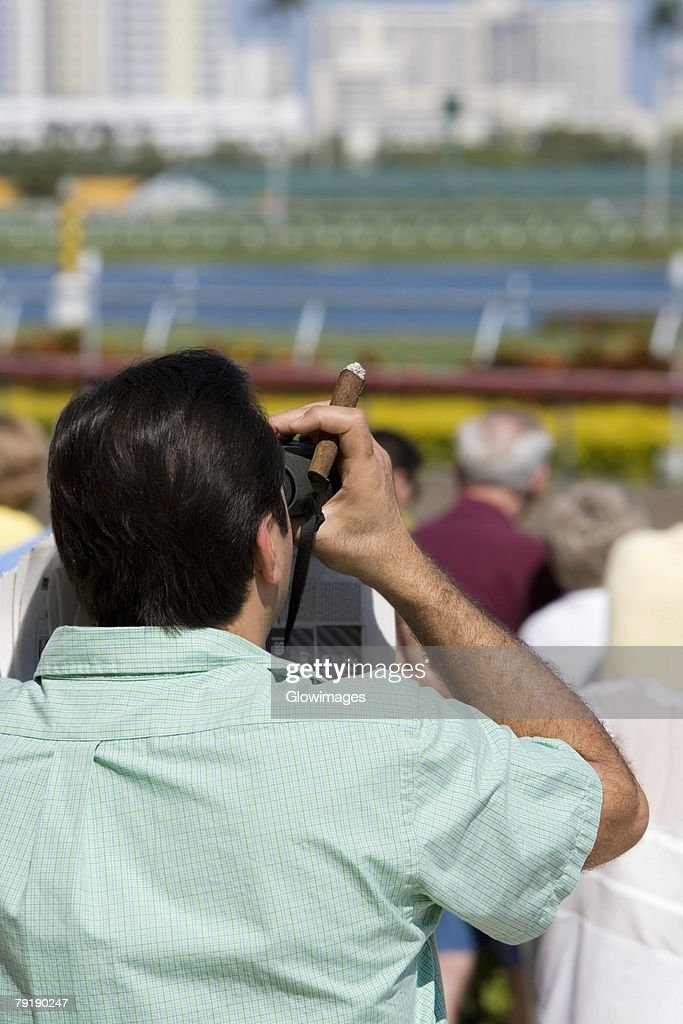 Rear view of a spectator looking through a pair of binoculars at the horseracing track : Foto de stock