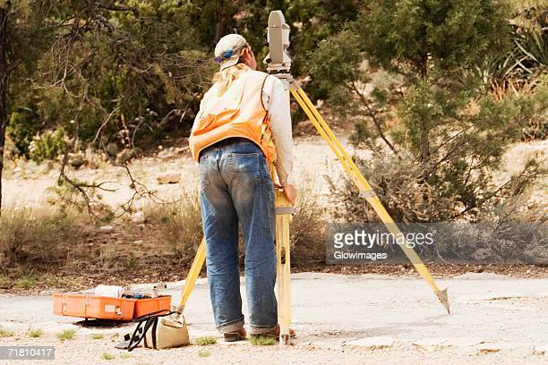 Rear view of a surveyor looking through a theodolite