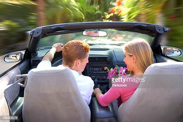 Rear view of a teen couple sitting in a convertible car getting ready to drive off.