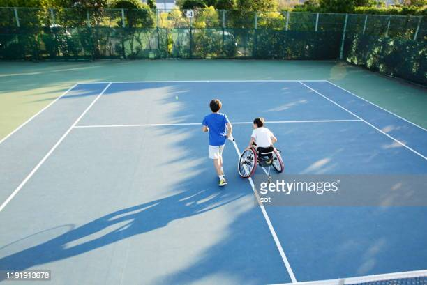 rear view of a teenage boy running with another teenage boy in a wheelchair on a tennis court - sport venue ストックフォトと画像