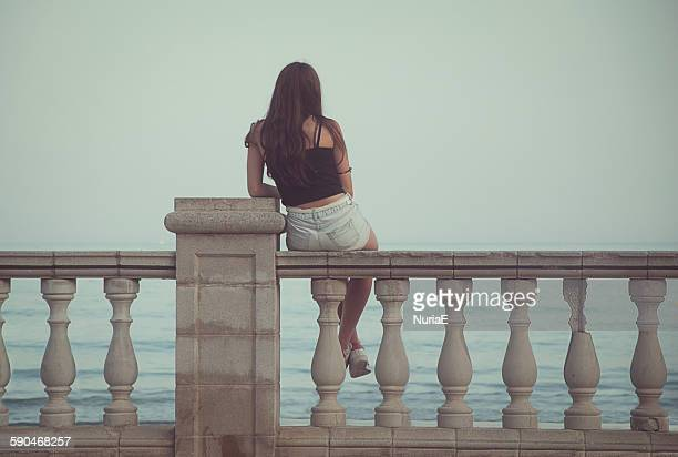 Rear view of a teenage girl sitting on a wall overlooking the sea