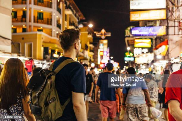 rear view of a tourist at khao san road in bangkok, thailand - rucksacktourist stock-fotos und bilder