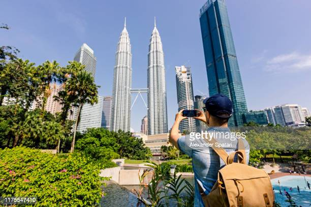 rear view of a tourist taking pictures of kuala lumpur skyline with smartphone, kuala lumpur, malaysia - kuala lumpur stock pictures, royalty-free photos & images
