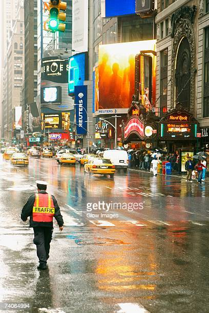 rear view of a traffic cop walking on the road - traffic cop stock pictures, royalty-free photos & images