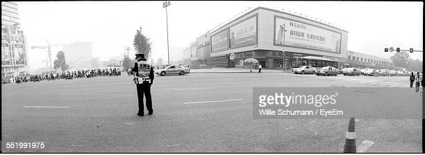 rear view of a traffic police standing on road - traffic cop stock pictures, royalty-free photos & images