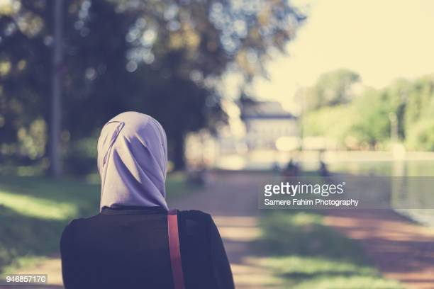rear view of a veiled muslim woman walking in forest - veil stock pictures, royalty-free photos & images