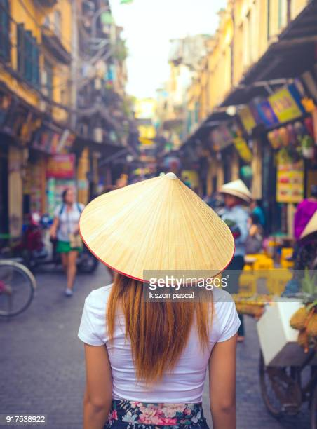 rear view of a vietnamese women with conical hat in a street of hanoi in vietnam - cappello conico stile asiatico foto e immagini stock