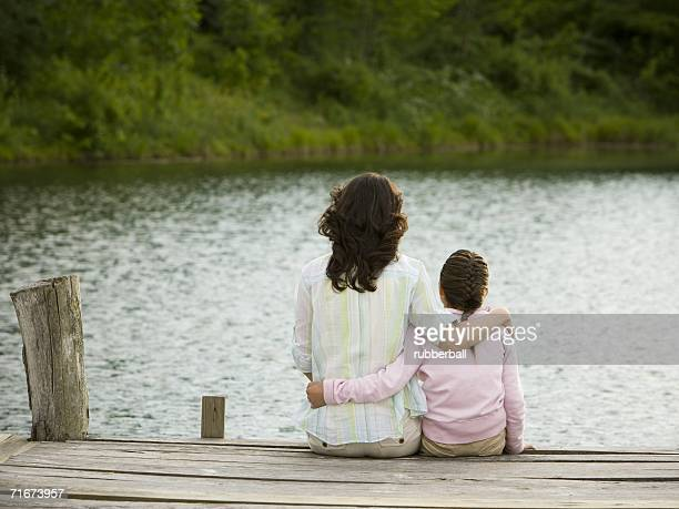 Rear view of a woman and her daughter sitting on a pier