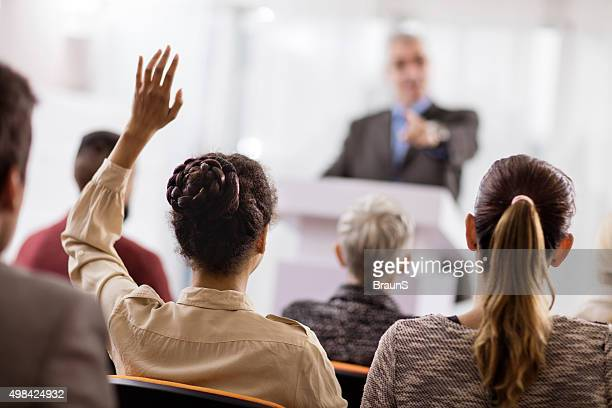Rear view of a woman asking a question on seminar.