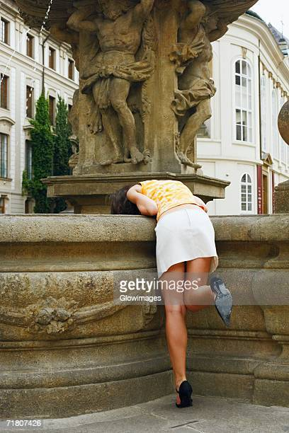 rear view of a woman bending over a fountain - bending over stock pictures, royalty-free photos & images