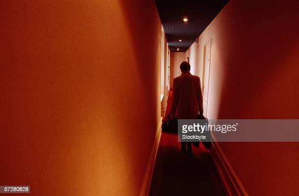Rear view of a woman carrying luggage down a corridor