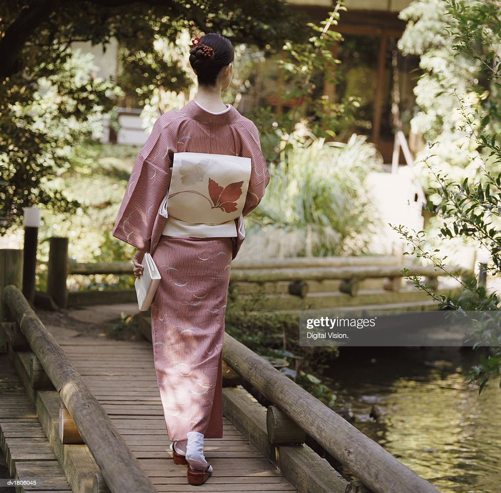 Rear View of a Woman Holding a Book and Walking on a Wooden Bridge : ストックフォト
