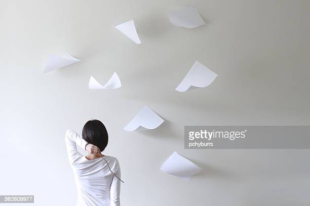 Rear view of a woman holding a stick behind her head with pieces of paper flying around