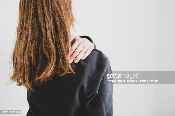 rear view of a woman holding her shoulder because of shoulder pain - injured stock pictures, royalty-free photos & images