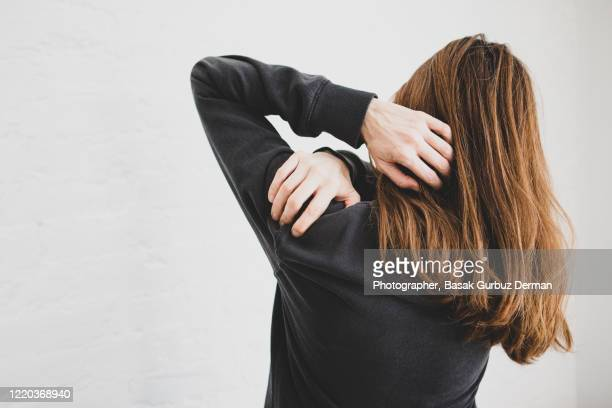 rear view of a woman holding her shoulder because of shoulder pain - pain stock pictures, royalty-free photos & images