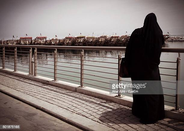 Rear view of a woman in burka looking at river