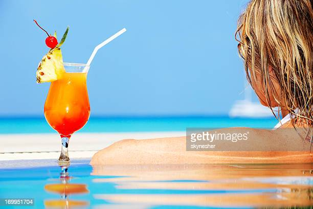 Rear view of a woman in infinity pool with cocktail.