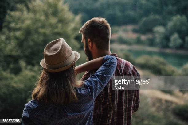 Rear view of a woman leaned on man's shoulder