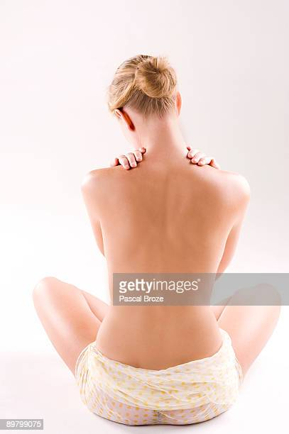 Rear view of a woman massaging her shoulders
