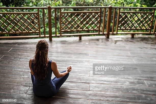 Rückansicht eines eine Frau Meditieren auf einem Balkon.