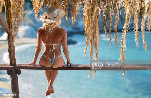 Rear view of a woman on wooden lath in summer.