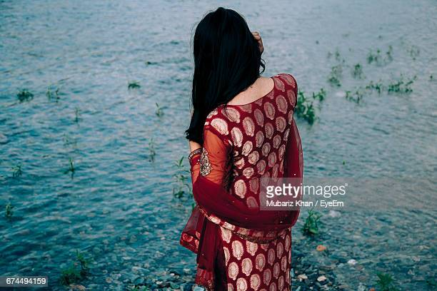 rear view of a woman overlooking calm water - salwar kameez stock pictures, royalty-free photos & images