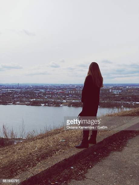 rear view of a woman overlooking river - nizhny novgorod oblast stock photos and pictures
