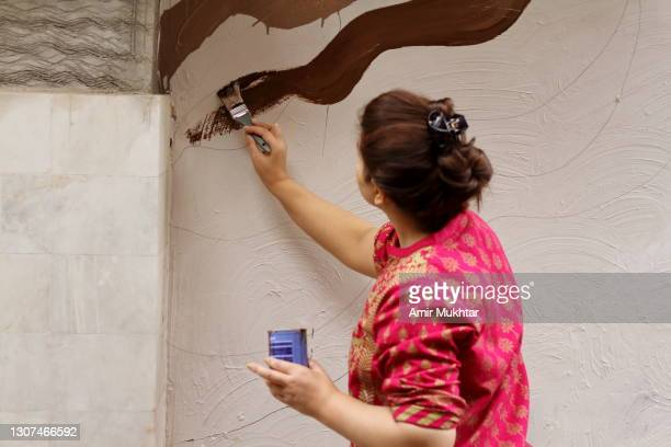 rear view of a woman painting on a wall. - printed sleeve stock pictures, royalty-free photos & images