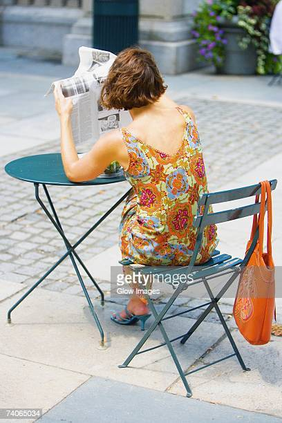 Rear view of a woman reading a newspaper