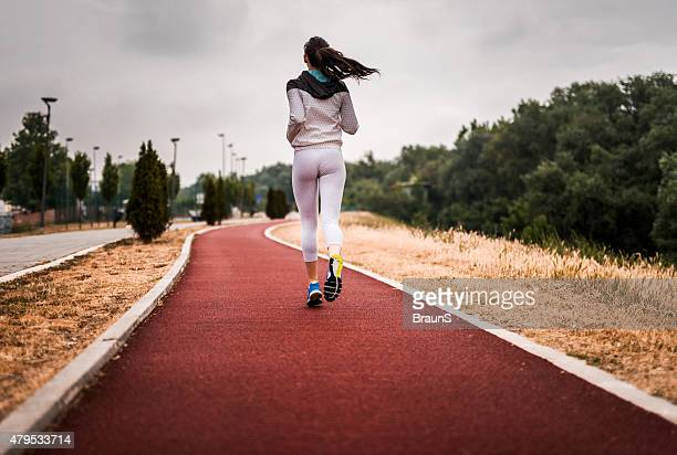 Rear view of a woman running on sports track.