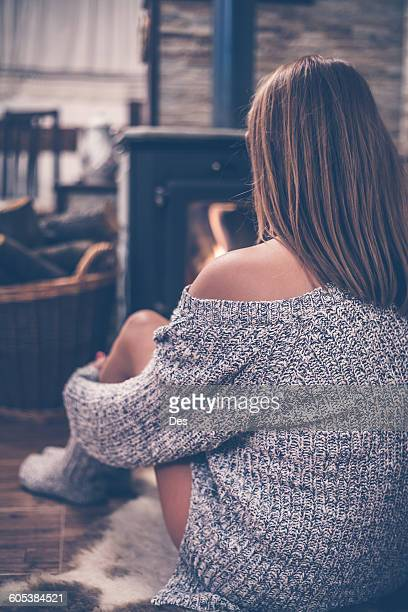Rear view of a woman sitting in front of a wood burning stove