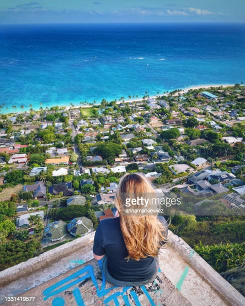 rear view of a woman sitting on a bunker looking at view of kailua bay, oahu, hawaii, usa - kailua stock pictures, royalty-free photos & images