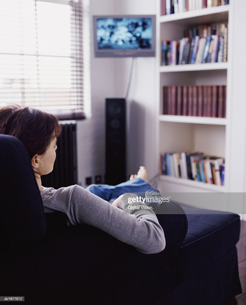 Rear View of a Woman Sitting on a Sofa and Watching TV : Foto de stock