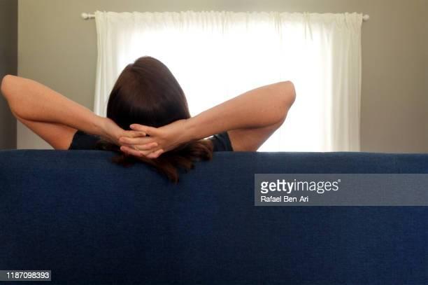 rear view of a woman sitting on sofa with hands behind head - rafael ben ari bildbanksfoton och bilder