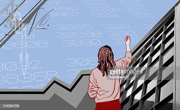 Rear view of a woman standing in front of stock market data