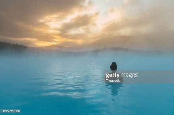 rear view of a woman standing in the blue lagoon, iceland - iceland stock pictures, royalty-free photos & images