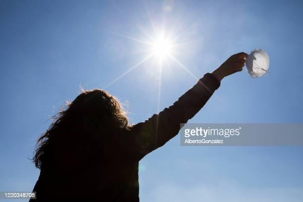 rear view of a woman standing outdoors removing her face mask, spain - strip bildbanksfoton och bilder