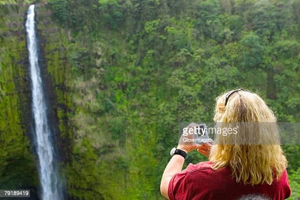 Rear view of a woman taking a photograph of a waterfall, Akaka Falls, Akaka Falls State Park, Hilo, Big Island, Hawaii Islands, USA