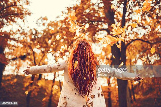 Rear view of a woman throwing autumn leaves.