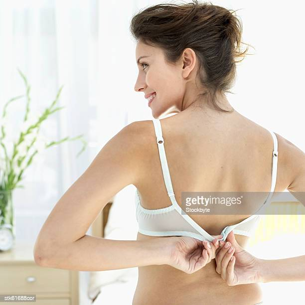 rear view of a woman unhooking her bra