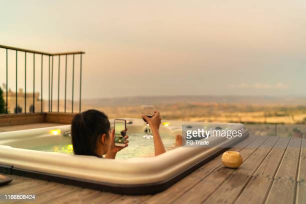 rear view of a woman using smartphone to take a picture while enjoying evening in a hot tub - hot tub stock pictures, royalty-free photos & images