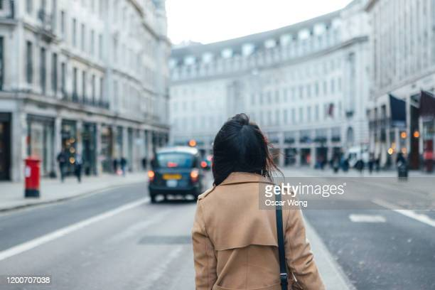 rear view of a woman waiting for uber on the high street in london - back stock pictures, royalty-free photos & images