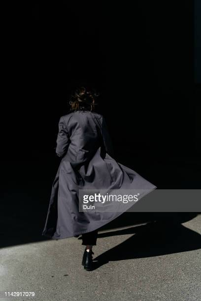 rear view of a woman walking away wearing a trench coat - trench coat stock pictures, royalty-free photos & images