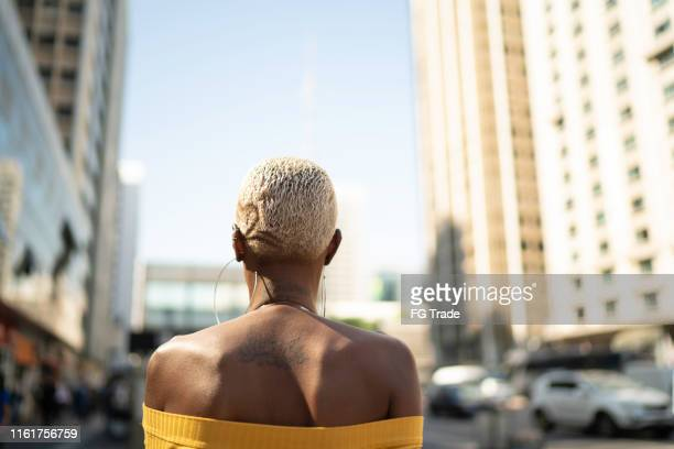 rear view of a woman walking in the city - shaved head stock pictures, royalty-free photos & images