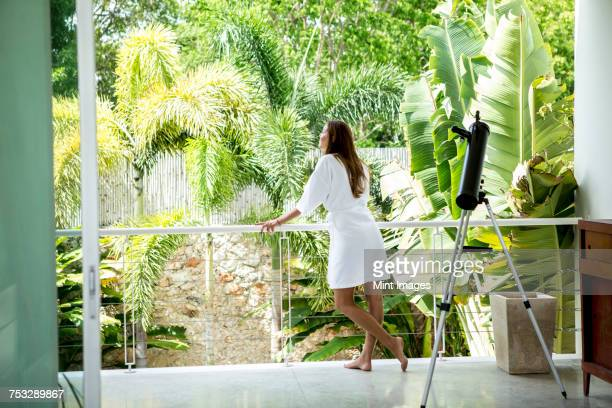 rear view of a woman wearing a bathrobe standing on a balcony next to a telescope. - lush stock pictures, royalty-free photos & images