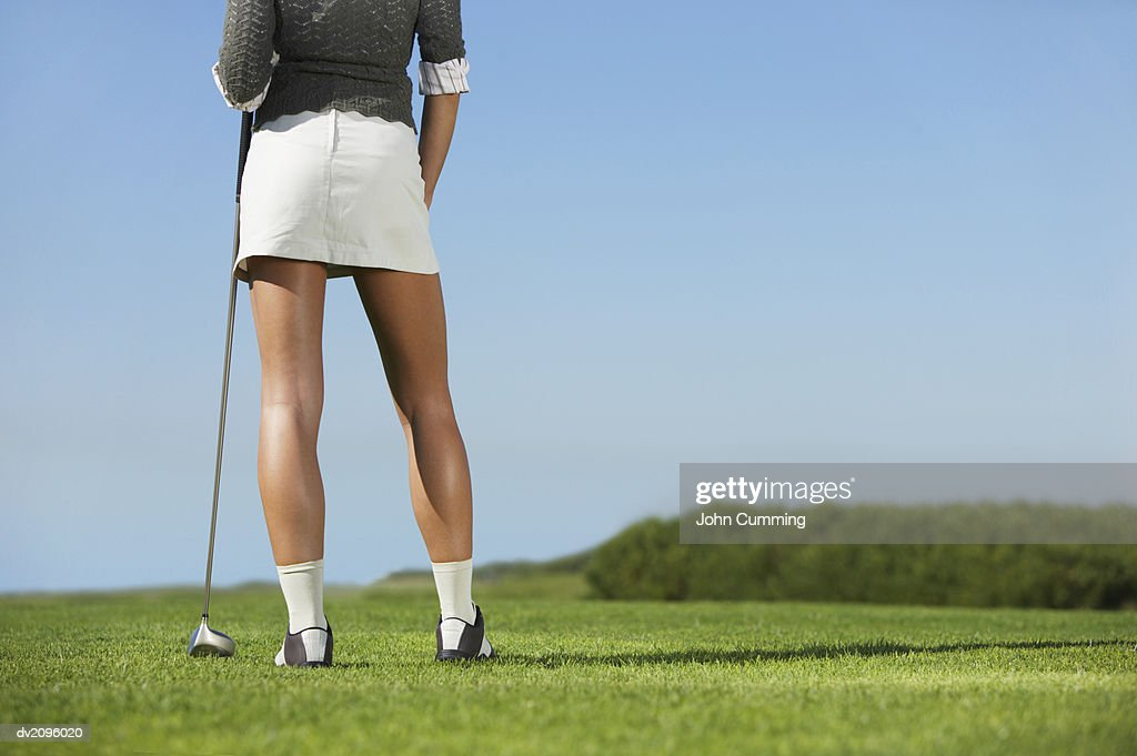 Rear View of a Woman Wearing a Mini Skirt on a Putting Green : Stock Photo