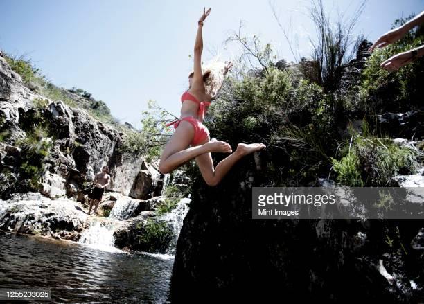 rear view of a woman wearing a red bikini jumping into a rock pool. - tidvattensbassäng bildbanksfoton och bilder