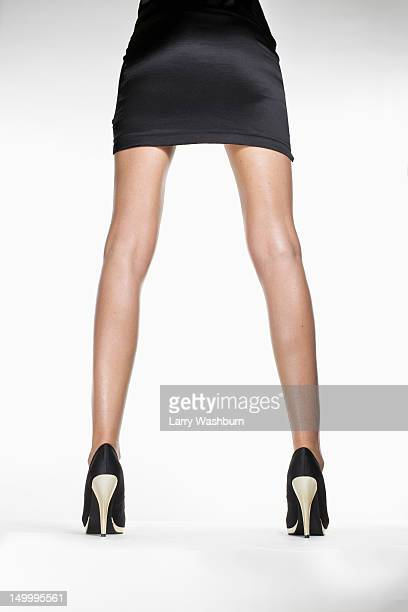 rear view of a woman wearing a skirt and high heels, waist down - legs spread woman stock photos and pictures